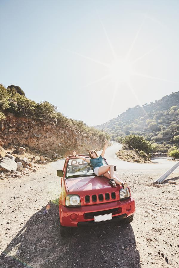 Girl on car bonnet. Happy beautiful carefree young woman having fun sitting on bonnet of convertible 4x4 car in mountains - road trip adventure concept royalty free stock photo