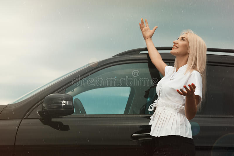 Girl at the car in the rain. Beautiful business woman girl near a car in the street is happy with the rain and the sun is shining stock image