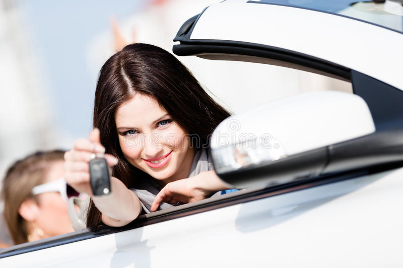 Girl in the car shows car key royalty free stock images