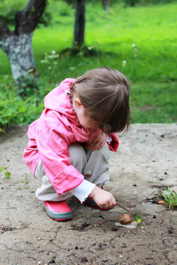 Girl is careful exploring the snail stock images