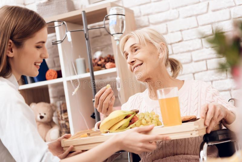 Girl is caring for elderly woman at home. Girl brings breakfast on tray. Woman is eating fruit. Girl is caring for elderly women in wheelchair at home. Girl stock image