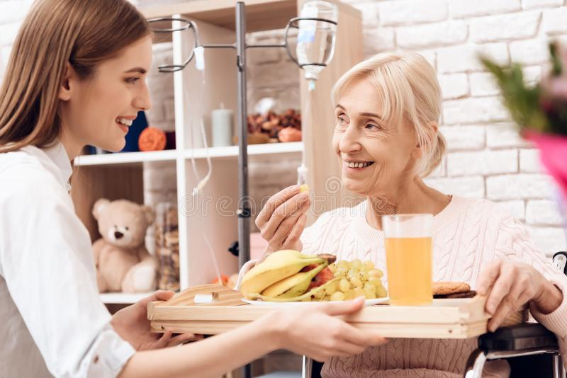 Girl is caring for elderly woman at home. Girl brings breakfast on tray. Woman is eating fruit. Girl is caring for elderly women in wheelchair at home. Girl royalty free stock photos