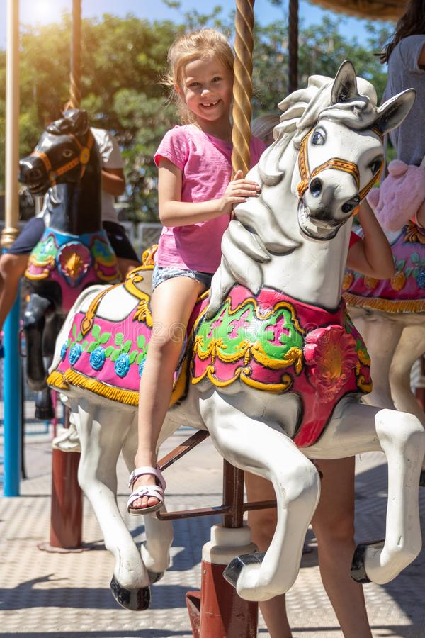 Girl on a carousel in an amusement park stock images
