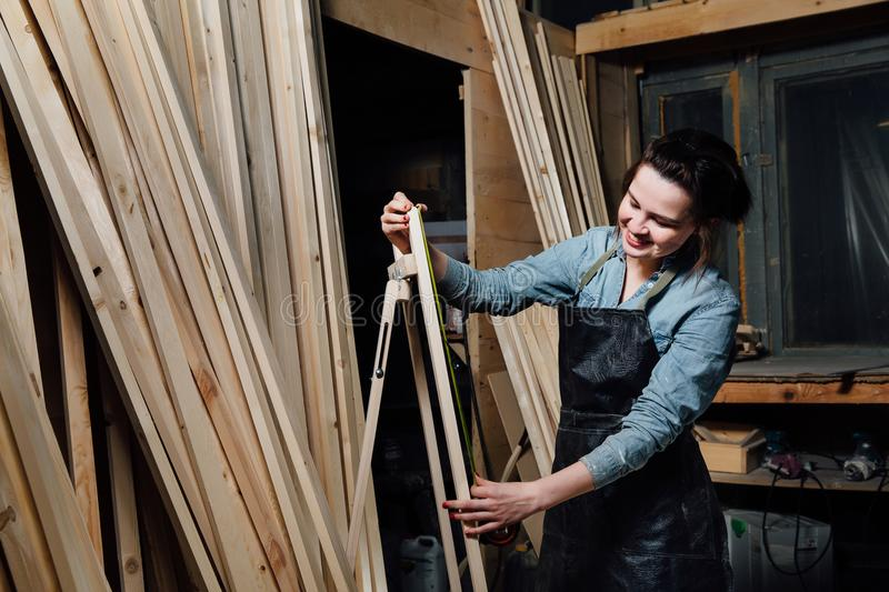 Girl carpenter with a tape measure on a background of wooden pieces in workshop. stock image