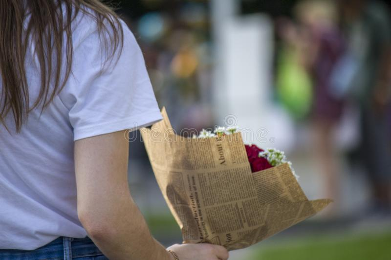 Girl with a bouquet goes through the park stock images