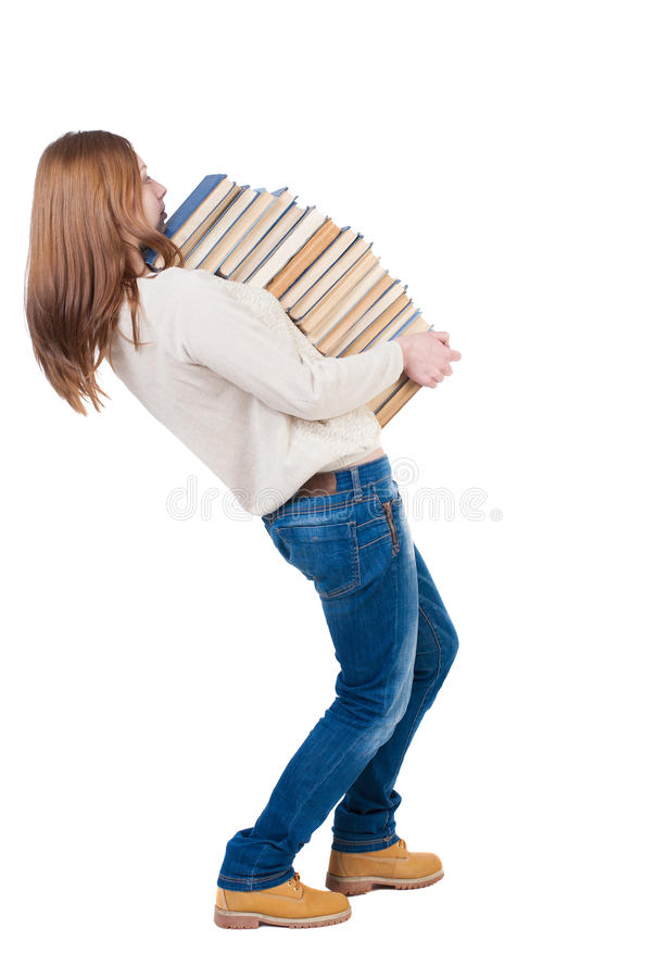 A girl carries a heavy pile of books. back view. Rear view people collection. A girl carries a heavy pile of books. Student goes form the library. back view stock images