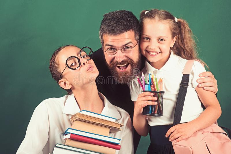 A girl carries a heavy pile of books. teacher and students with heavy stack book collection in hands royalty free stock image