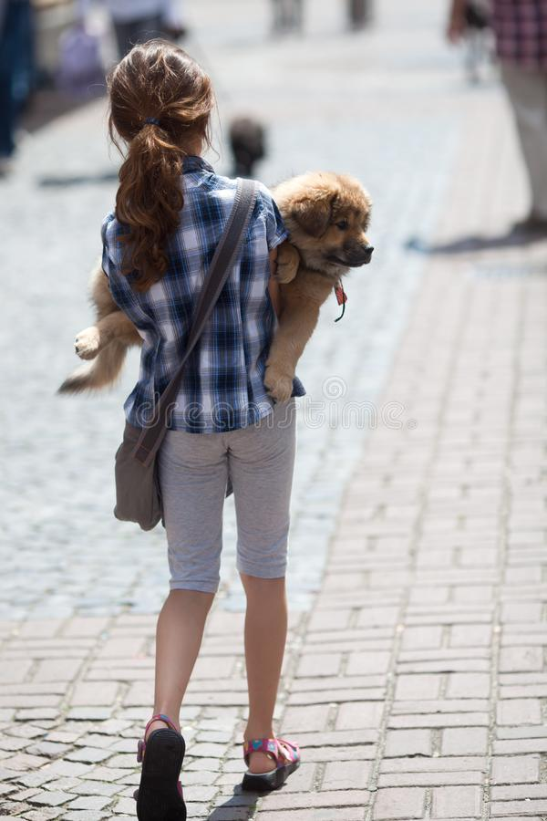 Girl carries her puppy