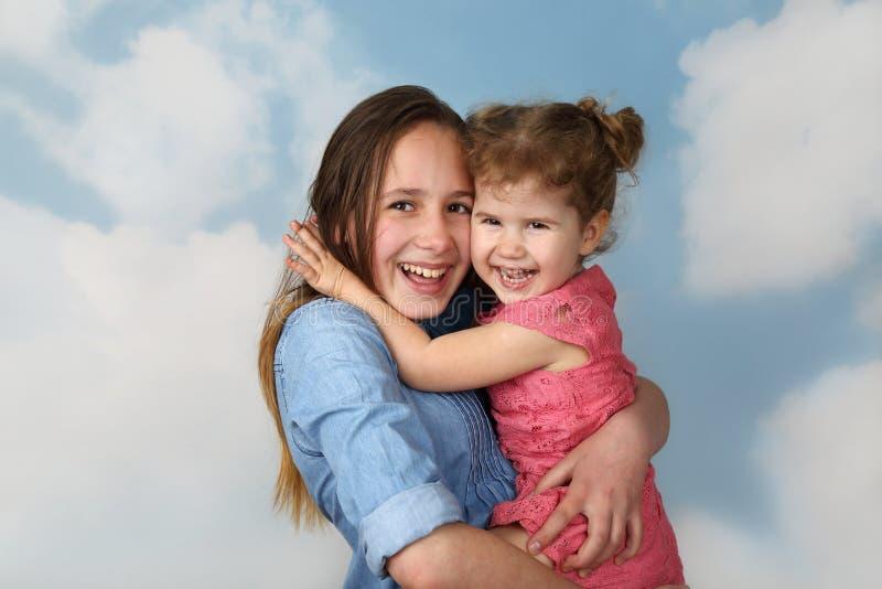 Girl carries little sister stock photos