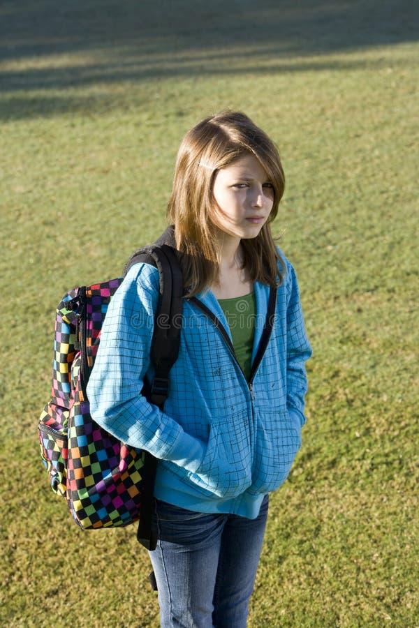 Girl carrying school backpack stock image