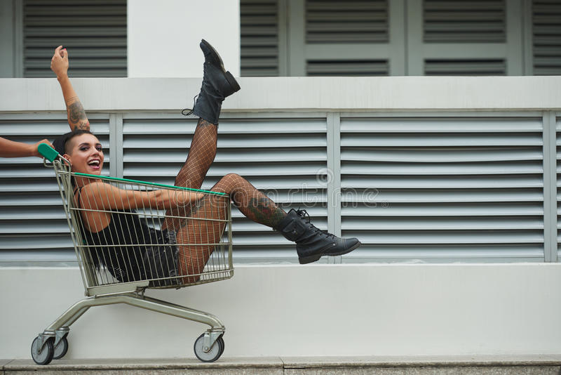 Girl in a cart. Carefree stylish girl sitting in shopping cart royalty free stock images