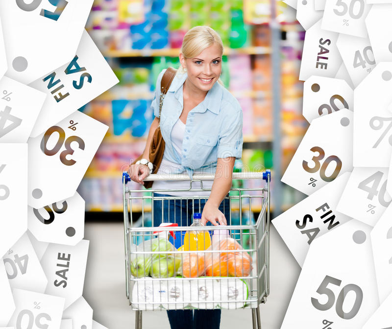 Girl with cart full of food in the shopping center. Sale coupons background royalty free stock photo