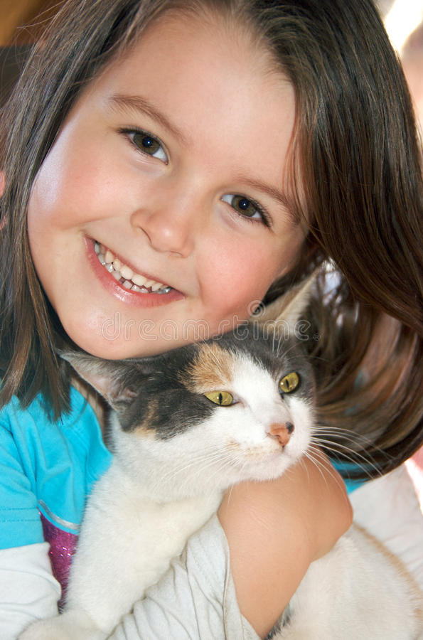 Girl with cat. Closeup portrait of little girl happily and tenderly hugging her cat