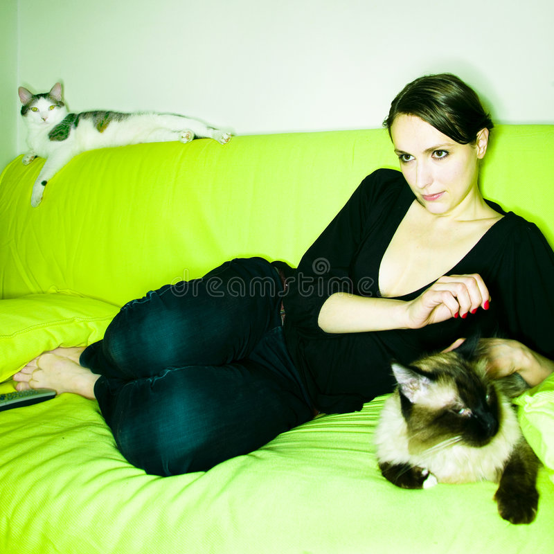 Girl with cat. Beautiful girl or young woman with her lazy cat, on sofa, watching TV and eating peanuts royalty free stock photography