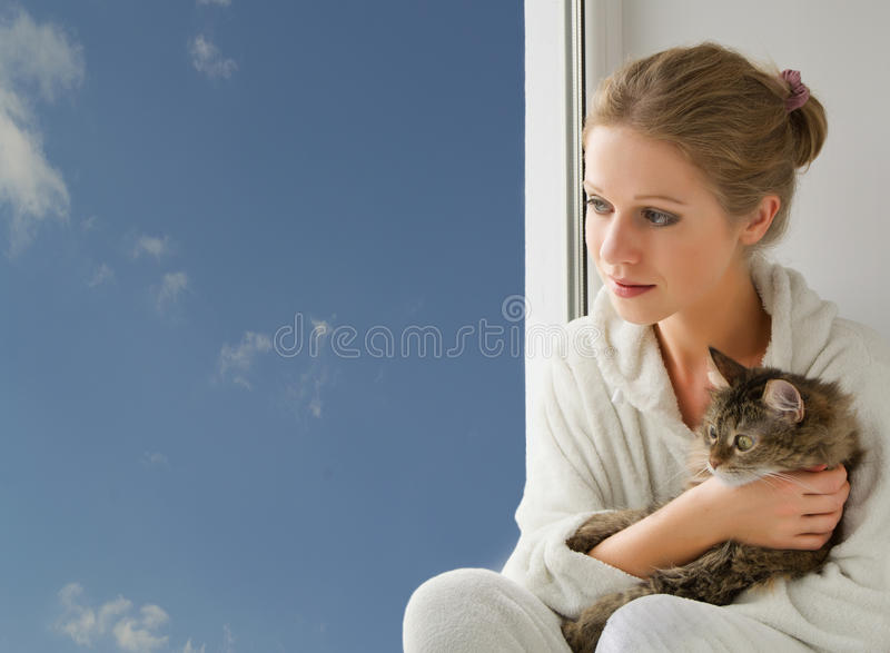 Girl with a cat looking out the window. Young beautiful girl with a cat in her arms looking out the window stock photo