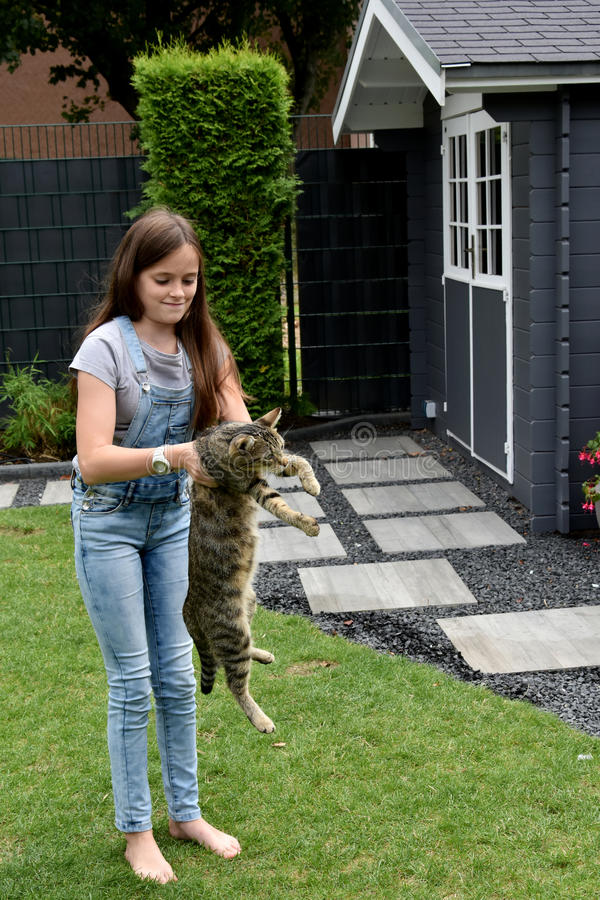 Girl and cat playing. Teenage girl playing with her young tabby cat royalty free stock images