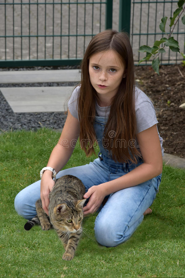 Girl and cat playing. Teenage girl playing with her young tabby cat stock images