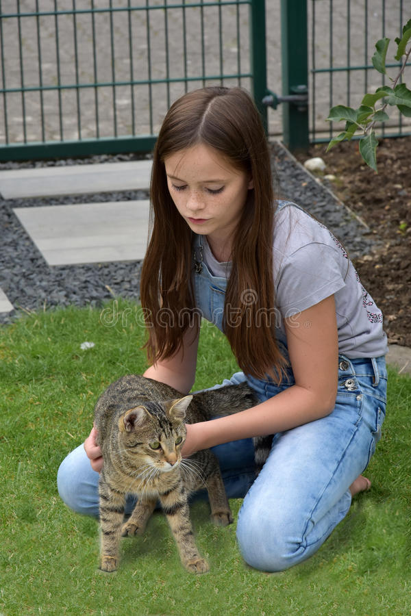 Girl and cat playing. Teenage girl playing with her young tabby cat royalty free stock image