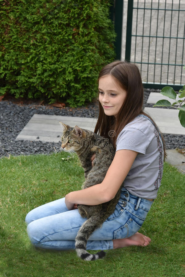 Girl and cat playing. Teenage girl playing with her young tabby cat stock photography