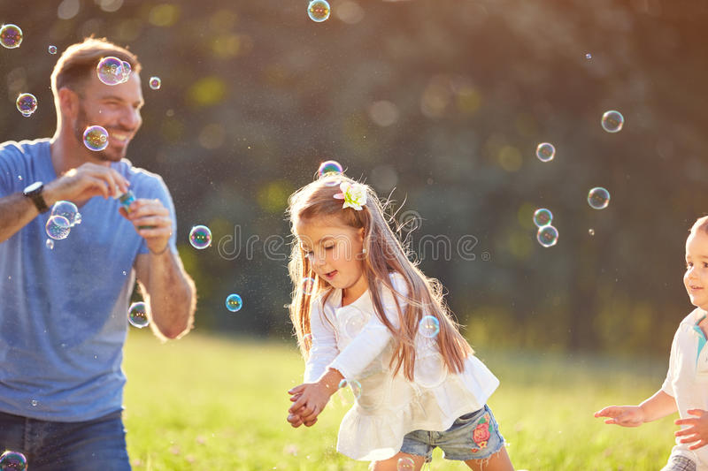 Girl catch soap bubbles outside. Cheerful girl catch soap bubbles outside royalty free stock images