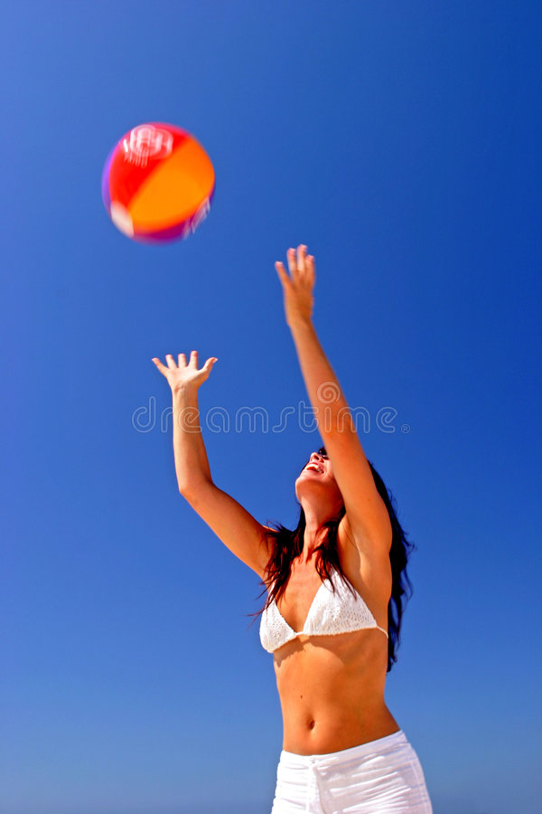 Girl catching beach ball on sunny beach in Spain with blue sky royalty free stock images