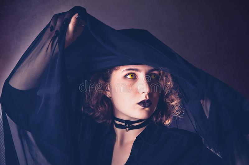 A girl of Caucasian appearance in black clothes with yellow eyes under a veil. Halloween, vampire costume royalty free stock image