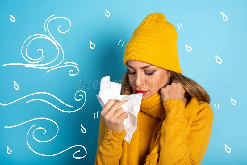Girl caught a cold and wipes her nose. Cyan background stock photo