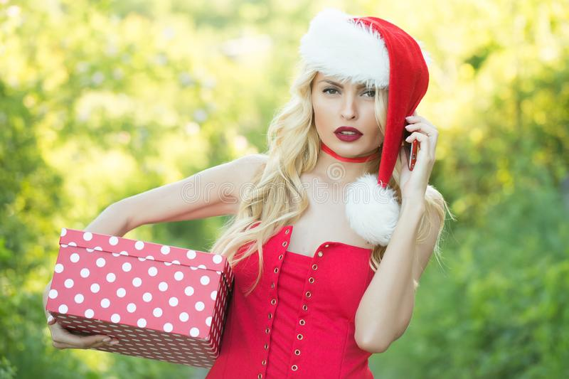 Girl celebrate new year with present box, mobile phone. Woman in santa hat with gift, greeting. Boxing day at Christmas. Xmas party, winter holiday. Christmas stock photography