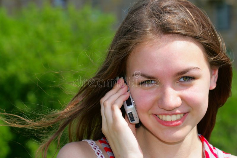 Girl with cell phone. Young smiling girl with cell phone, background is out of focus stock photo