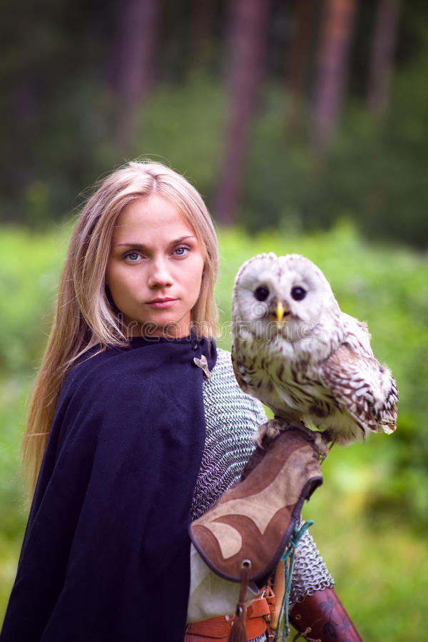 Girl in chain mail holding owl in forest.  stock image