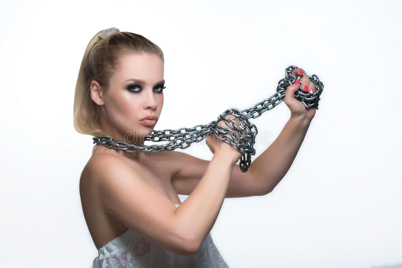 Girl with chains. Beautiful young woman with healthy and beautiful skin holding metal chains in her hands on white background royalty free stock photography