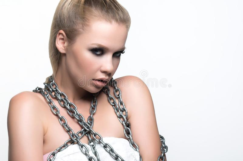 Girl with chains. Beautiful young woman with healthy and beautiful skin holding metal chains in her hands on white background stock photo
