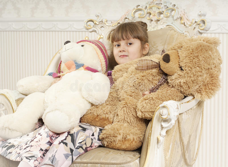 Girl in chair with a two bears stock photo