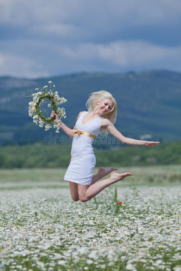Girl in chamomile field. Attractive blonde jumping with chamomile wreath in hand royalty free stock image