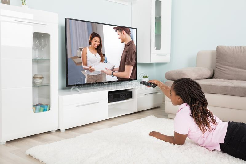 Girl Changing The Channel With Remote Control stock photos