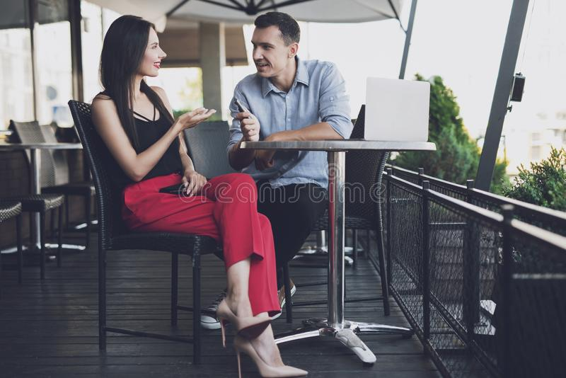 The girl is chatting with the journalist at the table. A reporter at work. The girl is talking with a journalist at a table in a restaurant, he is recording a stock photos