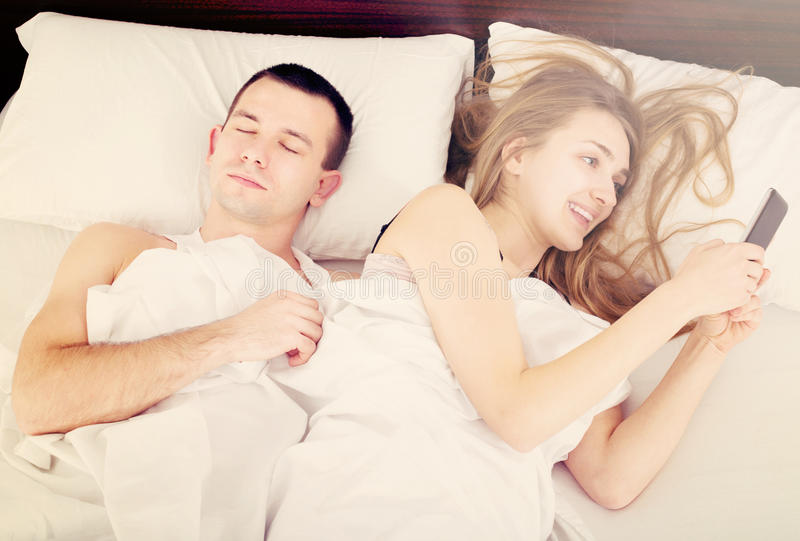 Girl chatting with mobile, man sleeping by in bed royalty free stock photography