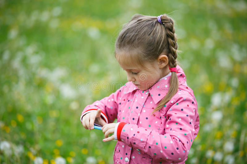 Girl checking photos she made with smart phone. Little girl checking and reviewing photos she made with smart phone camera, enjoying her time on a dandelion stock photos