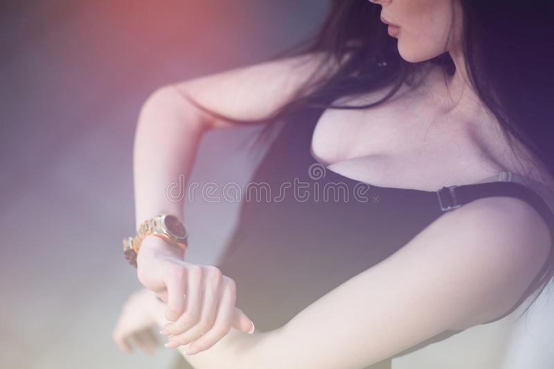 Cute girl checking time by looking at expensive gold watch on her wrist hand stock photos