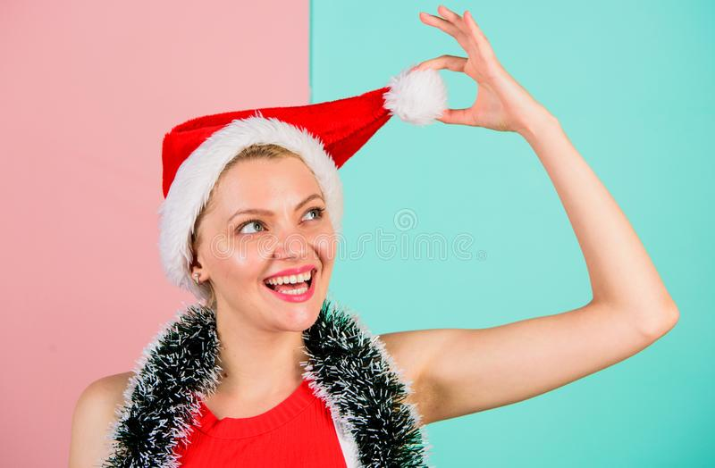 Girl cheerful face celebrate christmas. Woman with tinsel celebrate winter holiday christmas party. Woman in christmas. Santa hat play with pompon pink and blue stock photos