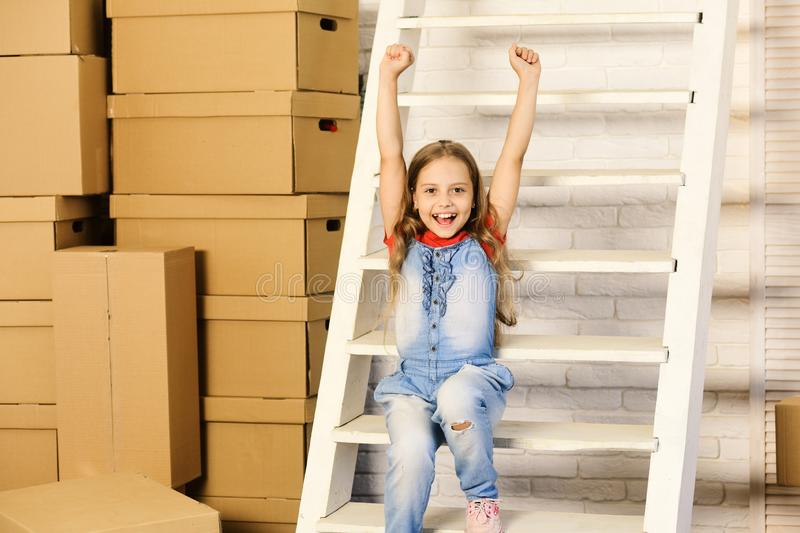 Girl with cheerful face with stairs and pile of boxes royalty free stock photography