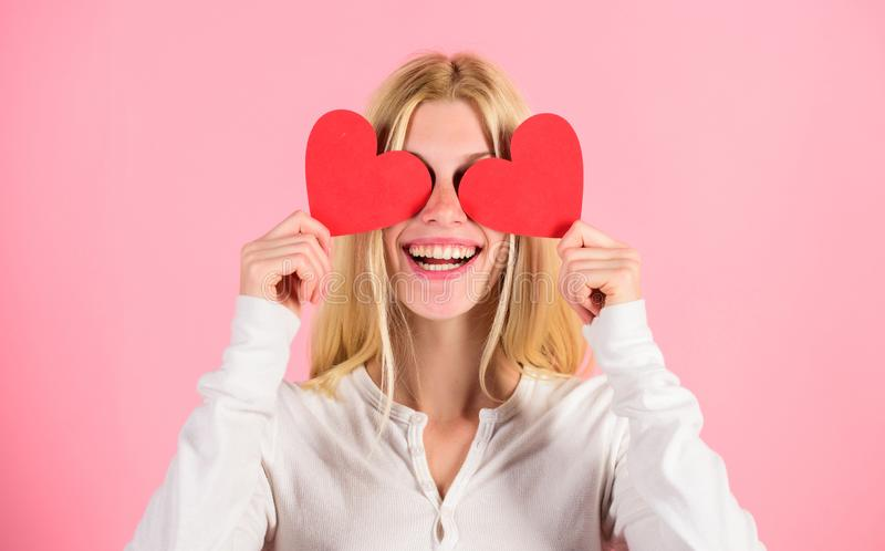 Girl cheerful fall in love. Girl hold heart symbol love and romantic pink background. Love is blind. Valentines day has. Traditionally been seen as more stock image