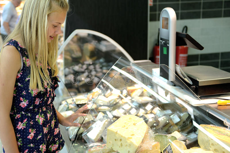Girl at cheese display in store. Young girl standing at a covered cheese display at a grocery store or supermarket royalty free stock photography