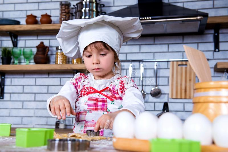 A girl in a chef`s hat is cooking gingerbread in the kitchen, making cakes from cookies tins stock images