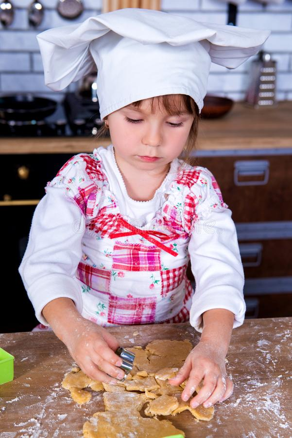 A girl in a chef`s hat is cooking gingerbread in the kitchen, making cakes from cookies tins stock photos