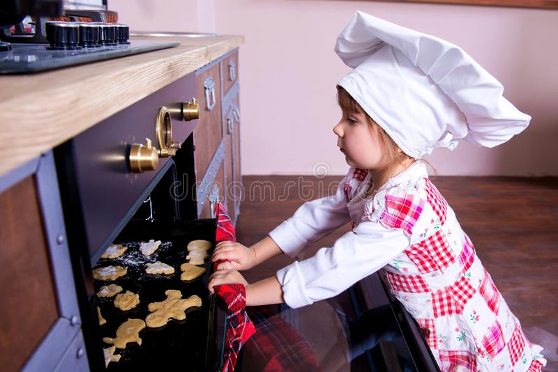 Girl in chef`s hat is putting gingerbread cookies in the oven royalty free stock image