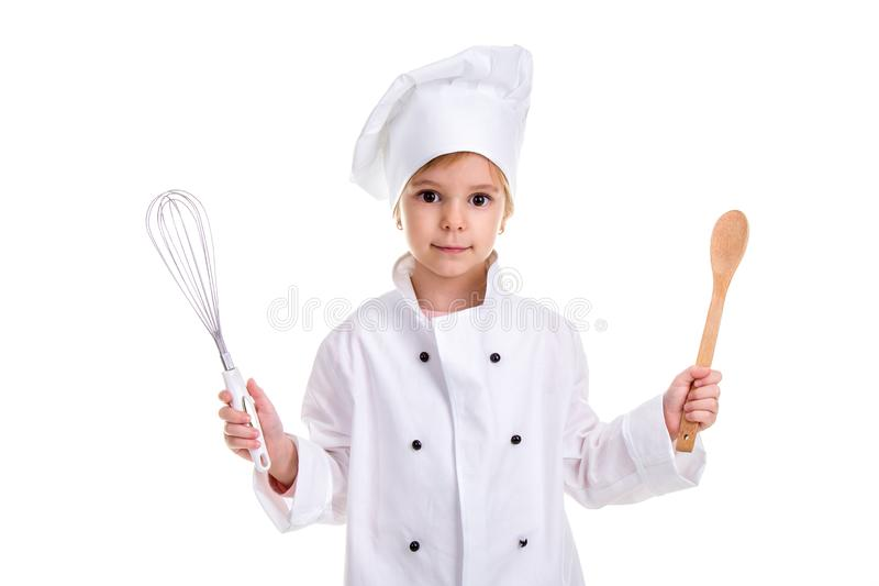 Girl chef white uniform isolated on white background. Holding the whisk in one hand and the other hand with a wooden. Spoon. Landscape image royalty free stock image