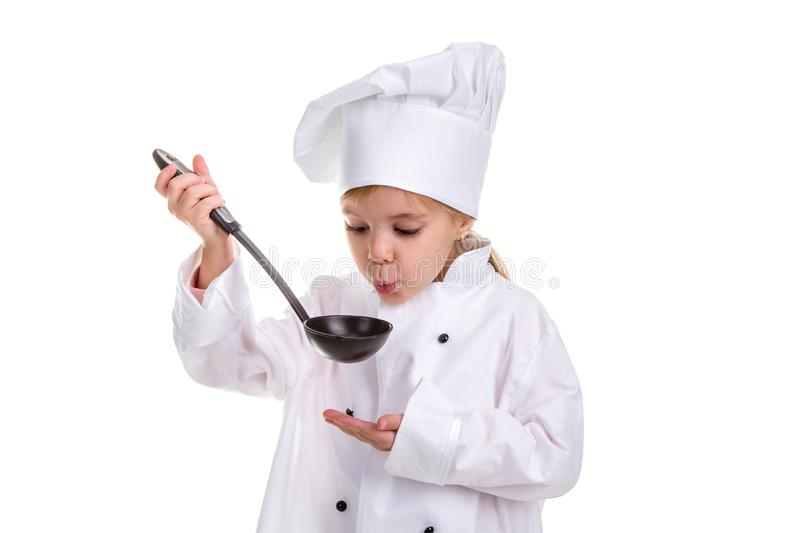 Girl chef white uniform isolated on white background. Holding black ladle and blowing to it. Looking at the ladle royalty free stock photography