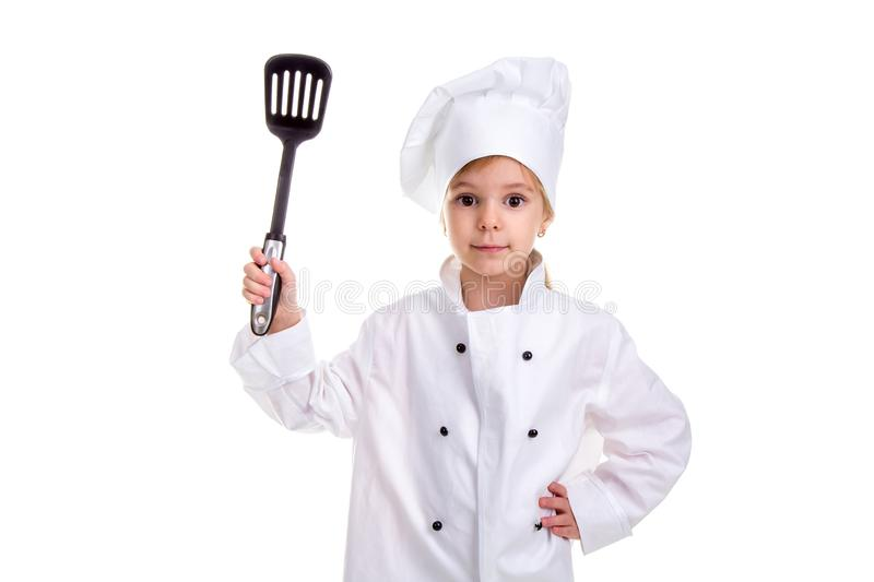 Girl chef white uniform isolated on white background. Holding black scapula up with another hand on the waist. Looking royalty free stock photography