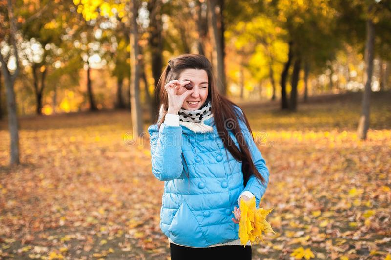 Girl with chestnut in hand. The girl holds a chestnut in his hand. Autumn theme. girl in the park in autumn.  stock image
